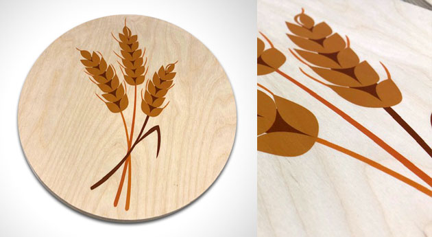 φωτογραφία με ένα στρογγυλό ξύλο που στο κέντρο έχει εκτύπωση με τρία στάχυα και δεξιά έχει λεπτομέρεια της εκτύπωσης σε ξύλο